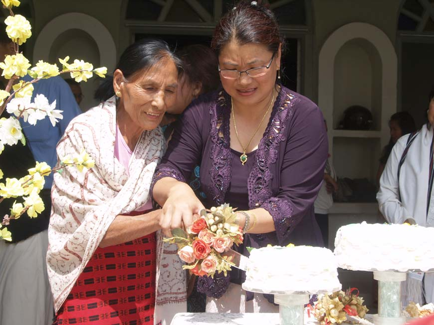 Mother of the year 2011, Rawonla Muivah being assisted by Elizabeth Thaisii in cutting the Mother' Day cake at MBC Church.