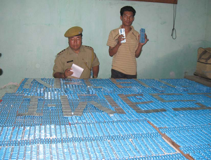 Arrested drug peddler, Md. Sahid-Ur-Rehman along with the seized SP tablets during a press conference held at the office of the Narcotic Cell of the Imphal West Police.