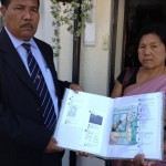 An album of Best wishes and greetings by EMA being opened by Bombyla's father and mother at London.