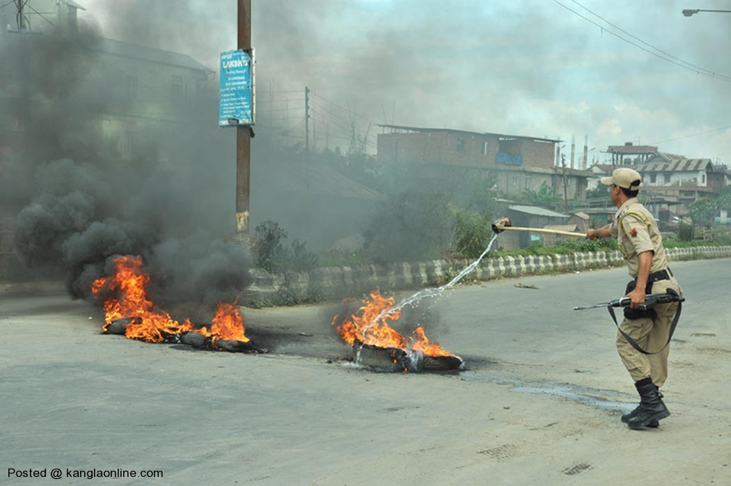 A police personnel tries to douse tyres burning along the Uripok road set ablaze by bandh supporters on Thursday.