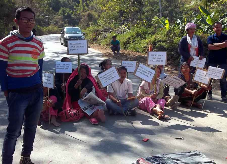 A boy stands in front of women bandh supporters seen holding placards along the Imphal-Moreh highway.