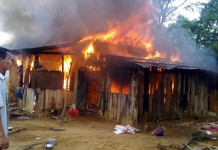 A man watches helplessly as a fire razes the house to the ground