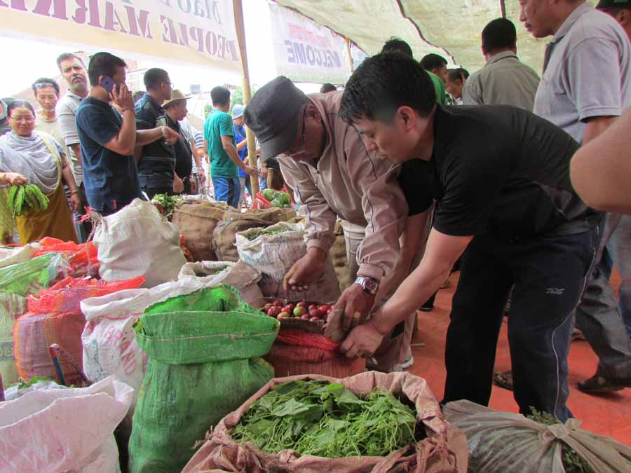 People checking the vegetables and fruits at the temporary market for Mao vendors.