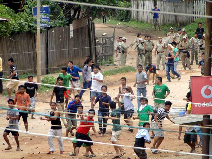 Police personnel turn a blind eye as protestors throw stones at a rally in Moreh