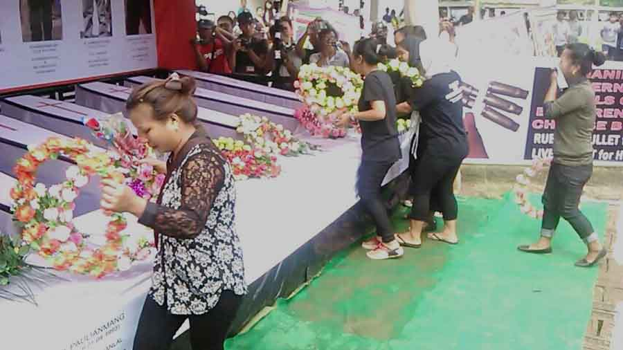 People offering floral wreaths at the symbolic coffins of the Ccpur martyrs.