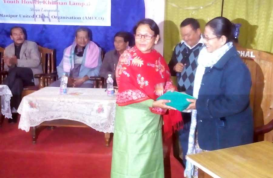 A Meitei girl from Myanmar recieving a gift during the reception programme. IFP Photo.
