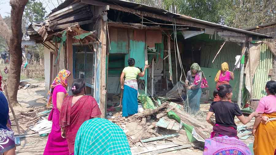 Locals dismantling the house of the alleged extortionists. IFP Photo