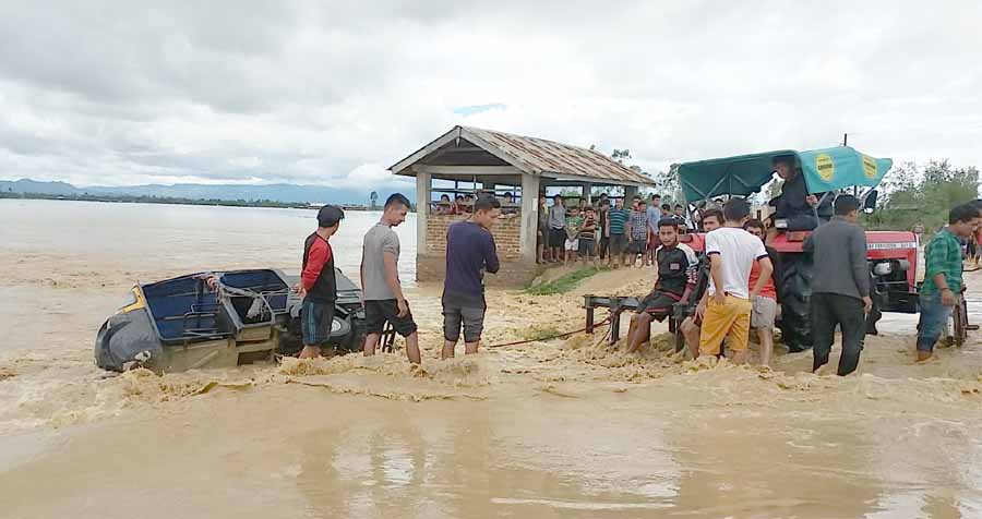 People attempting to pull back an auto rickshaw from turbulent flood waters at Kakching area. IFP Photo