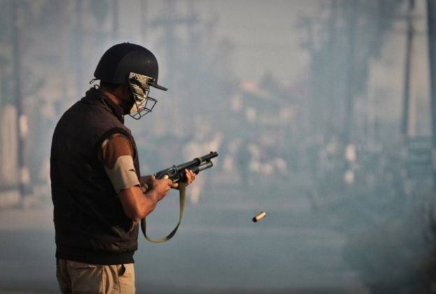 A policeman fires pellets to quell a protest in Srinagar