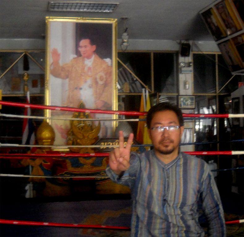 Oken Jeet Sandham at Bangkok Muaythai Institute, Rangsit, with King Bhumibol Adulyadej's huge image.