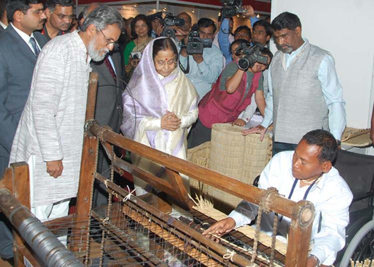 President Pratibha Devisingh Patil watching physically challenged innovator, Y. Mangi Singh from Kakching weave the Kouna Mat on his indegenously developed machine at the exhibition.