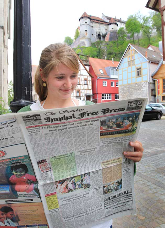 """IMPHAL FREE PRESS, March 6, 2011, issue being read in the German town of Heidenheim. This is part of a public art project by some academics in England and Ireland with the objective of connecting different outlying provinces of the world through the provincial media. IMPHAL FREE PRESS coordianted with HEIDENHEIMER ZEITUNG in Germany and had on March 6 carried a photo feature titled """"Where is Imphal?"""". This particular page was also reproduced in the HEIDENHEIMER ZEITUNG and circulated."""