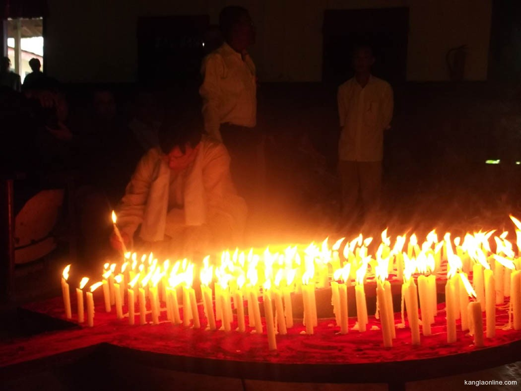 A participant lighting a candle during the Intl AIDS candlelight Memorial Day observation on Sunday at JN Dance Academy