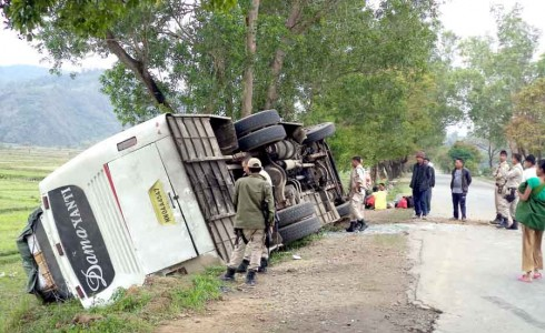 The bus lying overturned at the roadside.