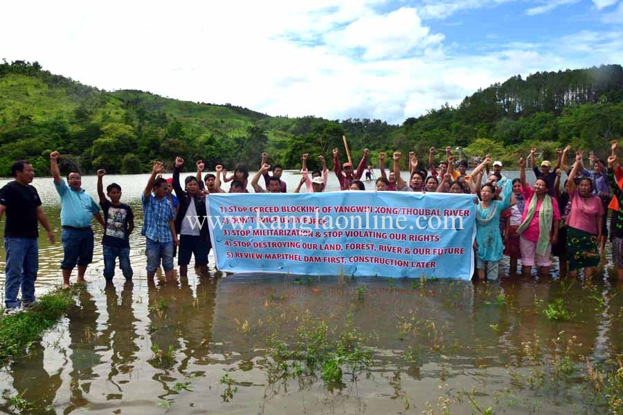 Villagers posed behind a banner demanding review of Mapithel Dam before its construction.