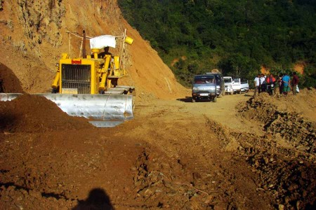 Vehicles wait while a bulldozer levels the road near Tengnoupal along the Imphal-Moreh highway.