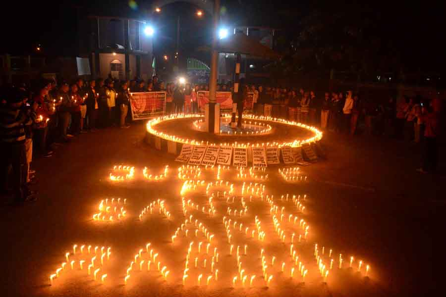 Students of Manipur University under the aegis of NEFIS taking out a candle light vigil up to the university main gate.