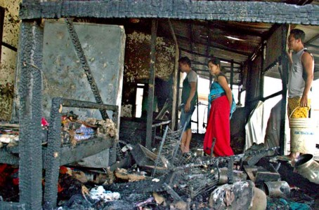 A family rummages through the remnants of their home which was burned down during the Mayai Lambi general strike. IFP Photo