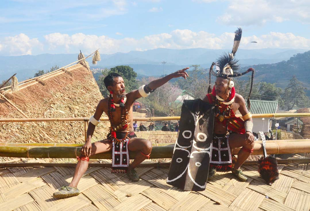 Naga tribesman gesture as they rest after their performance in front of their Morung on the second day of the state annual Hornbill Festival at Naga Heritage village Kisama, some 15 kms away from Kohima, Nagaland on Friday, December 02, 2016. Photo by Caisii Mao