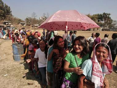 A woman shields herself from the sun with an umbrella as she and others queue to cast their vote at a polling station at Byrnihat, in the Ri-Bhoi district in the eastern Indian state of Meghalaya February 23, 2013. The states of Meghalaya and Nagaland went to the polls to elect members to the state assembly on Saturday. REUTERS/Utpal Baruah (INDIA - Tags: POLITICS ELECTIONS)